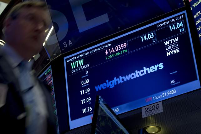 A trader passes by the ticker for Weight Watchers International Inc displayed on a screen on the floor of the New York Stock Exchange October 19, 2015. REUTERS/Brendan McDermid