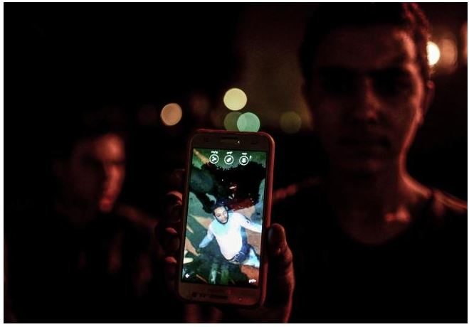 A man shows a photo he took on his mobile phone of a driver who was killed by a police officer. Credit: US News