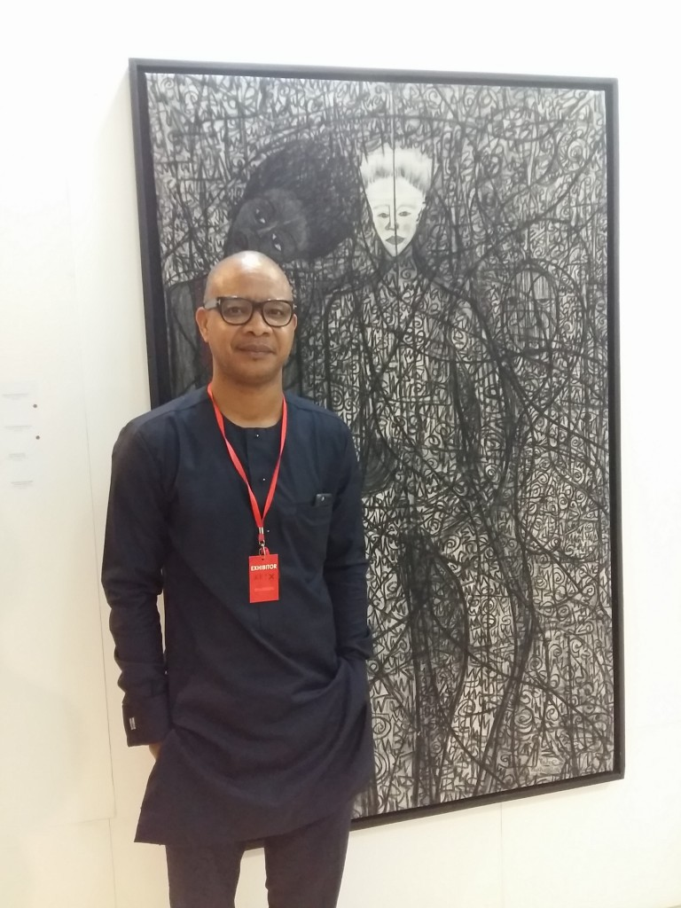Contemporary Artist, Victor Ehikhamenor, with one of his exhibitions at the ART X Lagos fair.